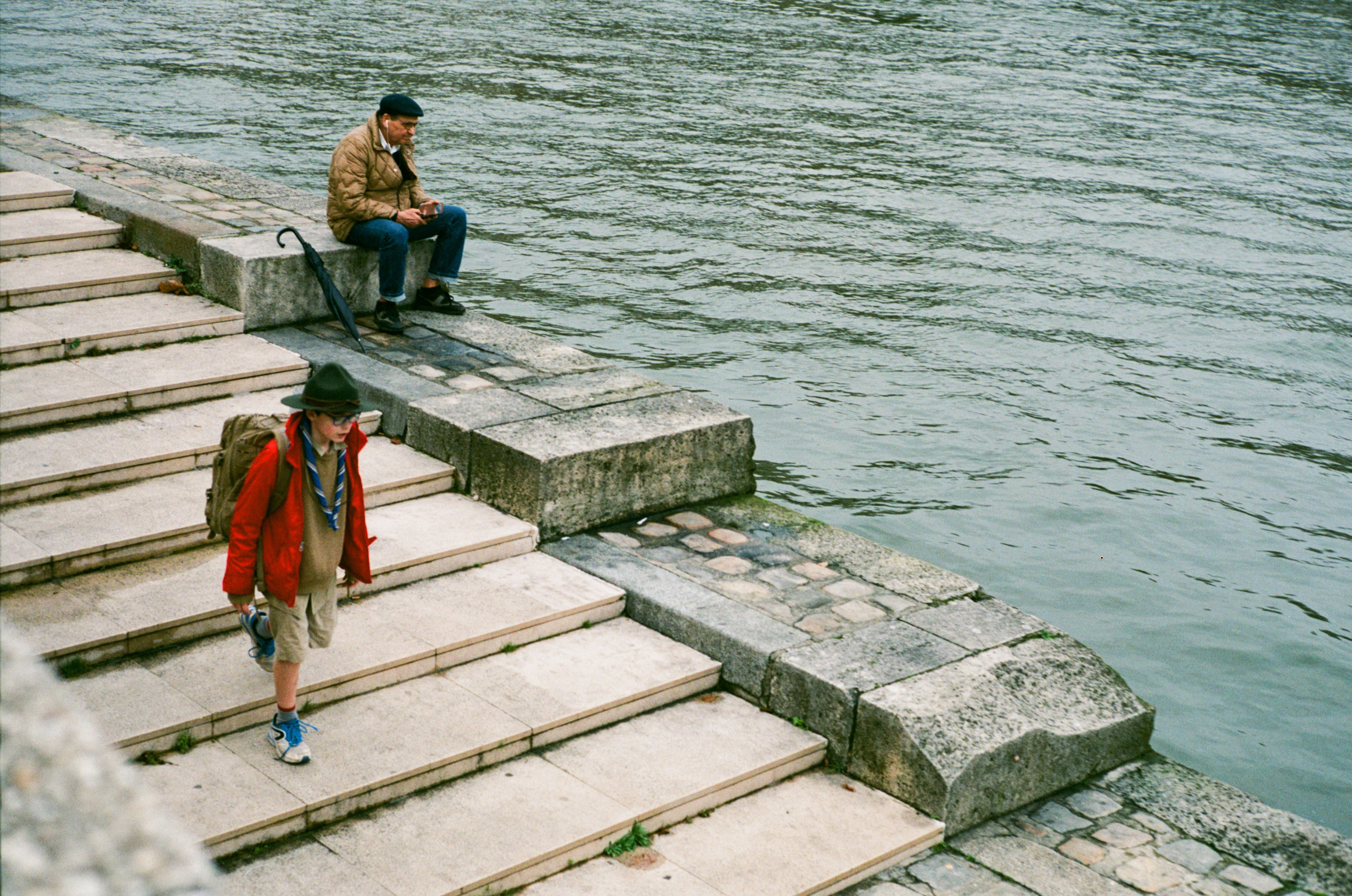 Dressed up young scout walking down stairs Seine left bank