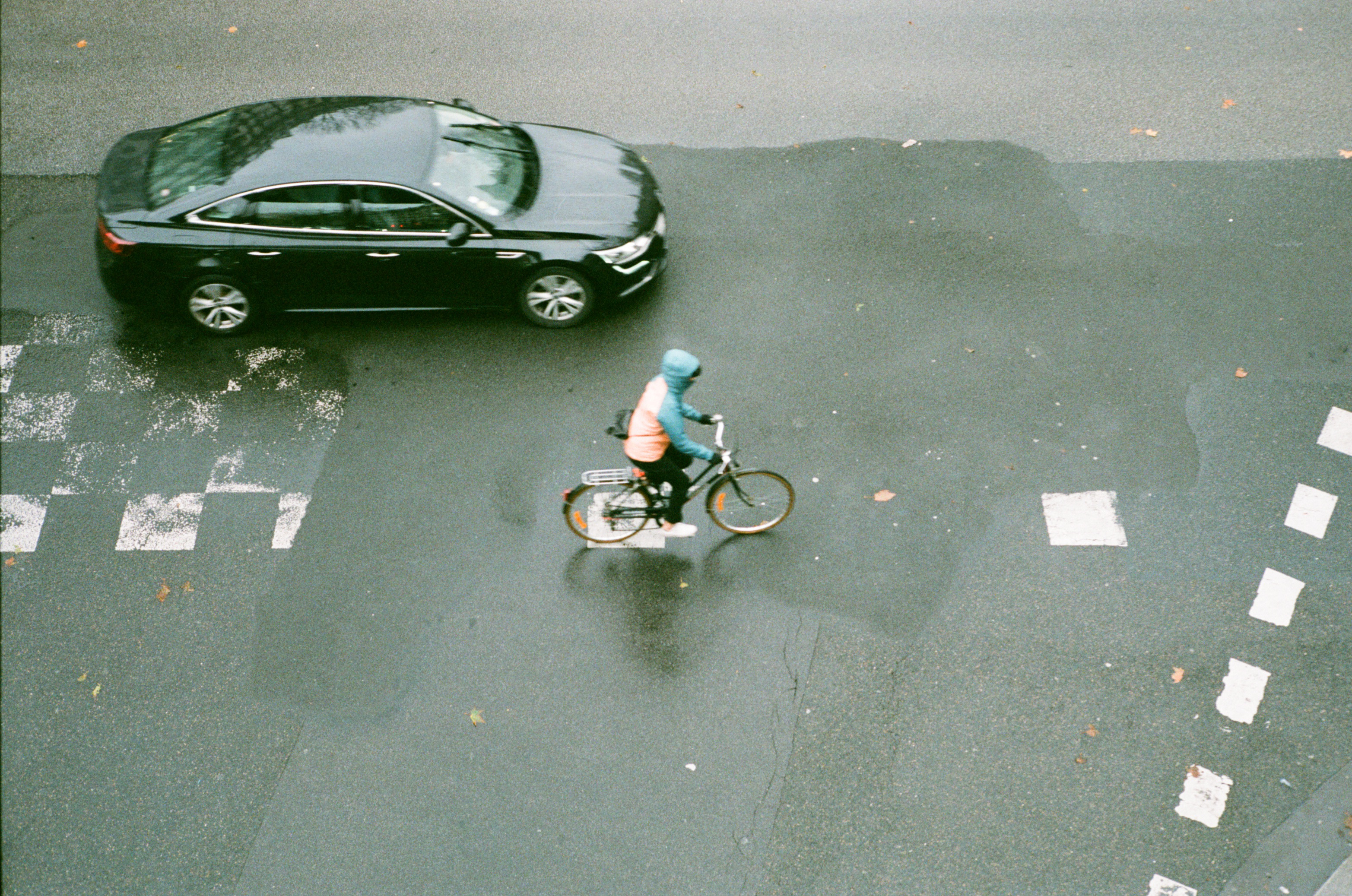 Cyclist commuting in Paris with a raincoat